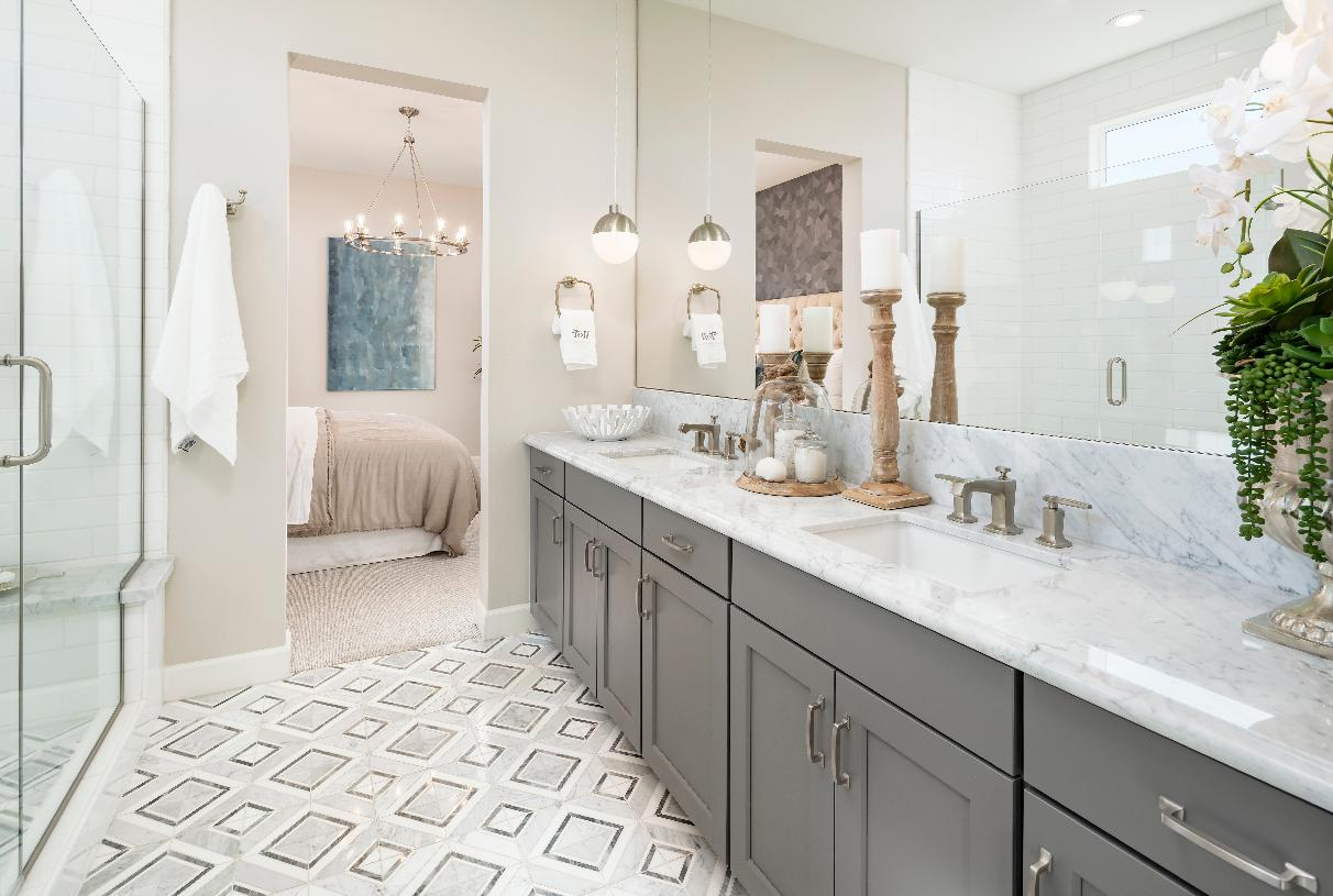 Spa-like primary bathroom with dual-sink vanity, oversized walk-in shower, and a patterned tile floor