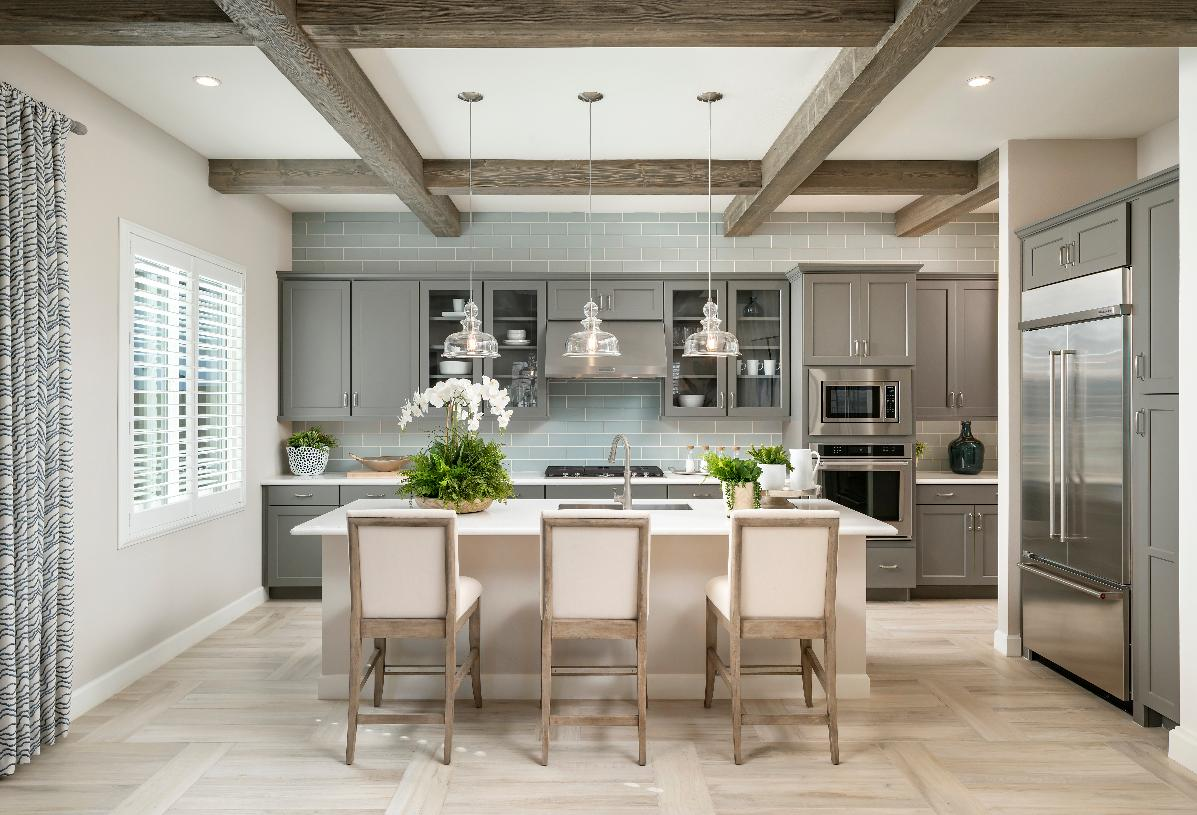 Well-appointed kitchen with center island, stainless steel appliances, subway tile backsplash and coffered ceiling