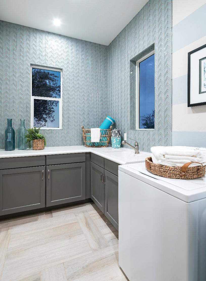 Centrally located laundry room with sink and storage