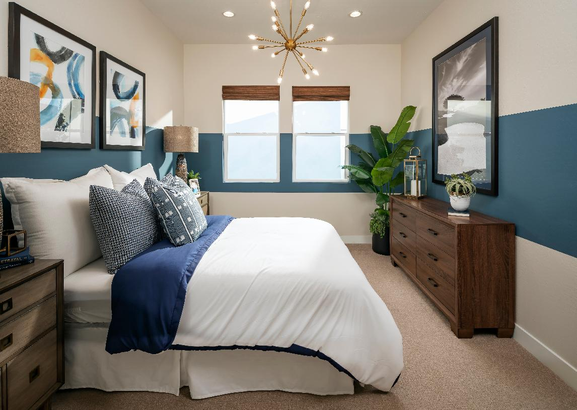 Secondary bedroom with bold paint detail and chandelier