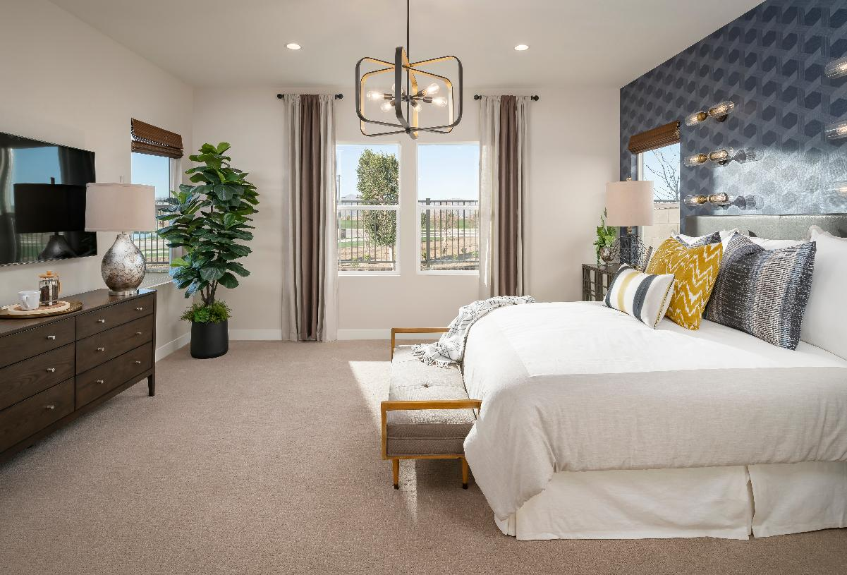 Primary bedroom suite with accent wall and chandelier