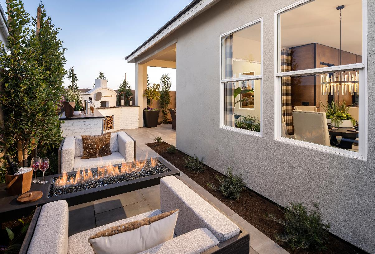 Beautiful outdoor gathering area with cozy fire place and pizza oven