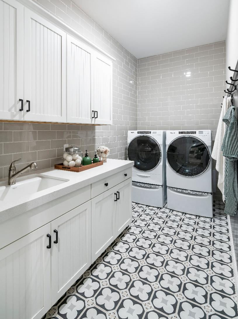 Laundry room with white cabinets, subway tile, quartz countertops and single basin sink