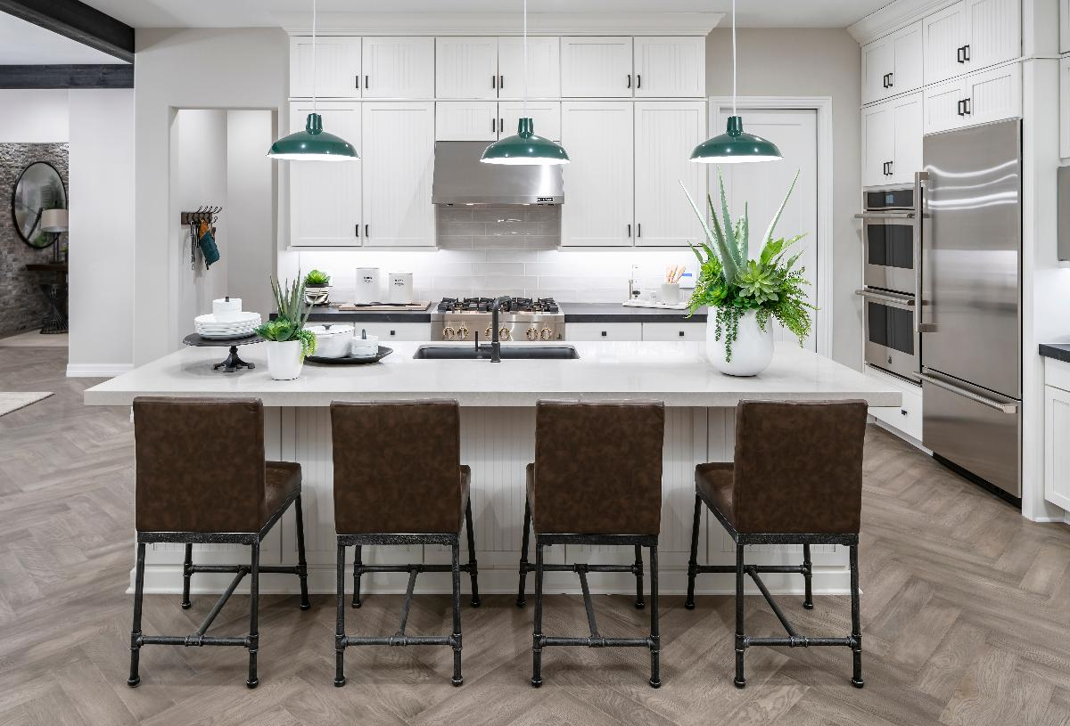 Elegant white kitchen with stainless steel appliances and large wet island