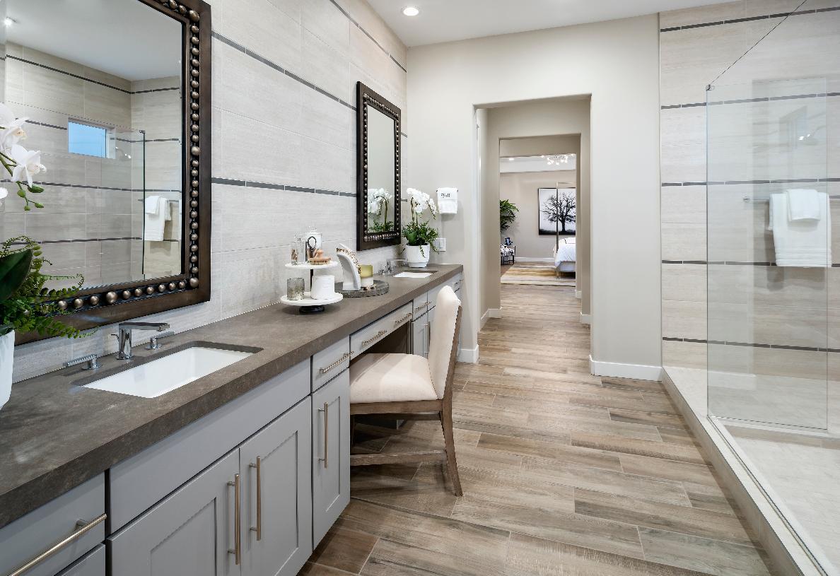 Primary bathroom with dual-sink vanity, large walk-in shower, and wood-look tile flooring