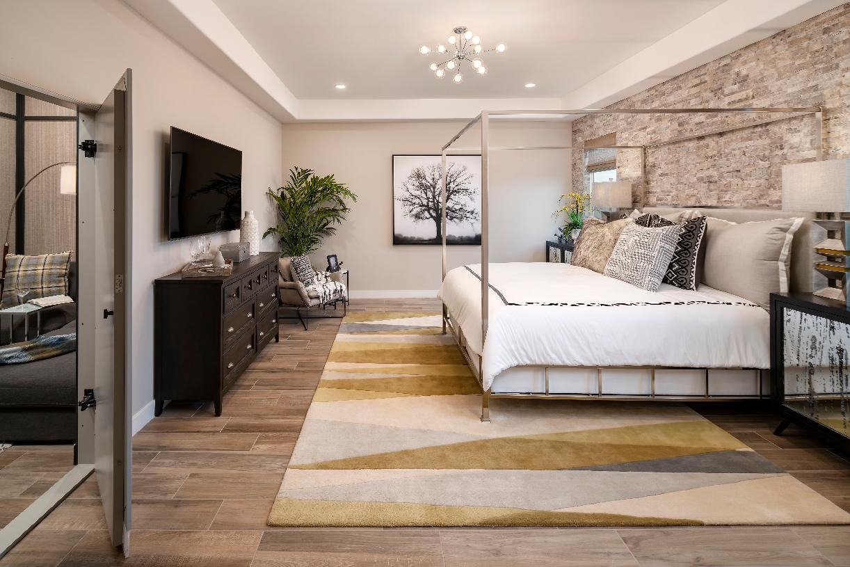 Primary bedroom suite with stone accent wall and direct access to adjacent pocket office