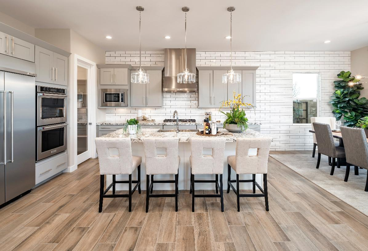 Gourmet kitchen with large center island, stainless steel appliances, and roomy walk-in pantry