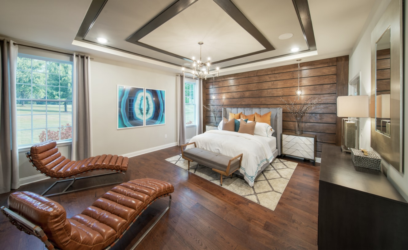 Secluded primary bedroom suite with tray ceiling and large walk-in closet