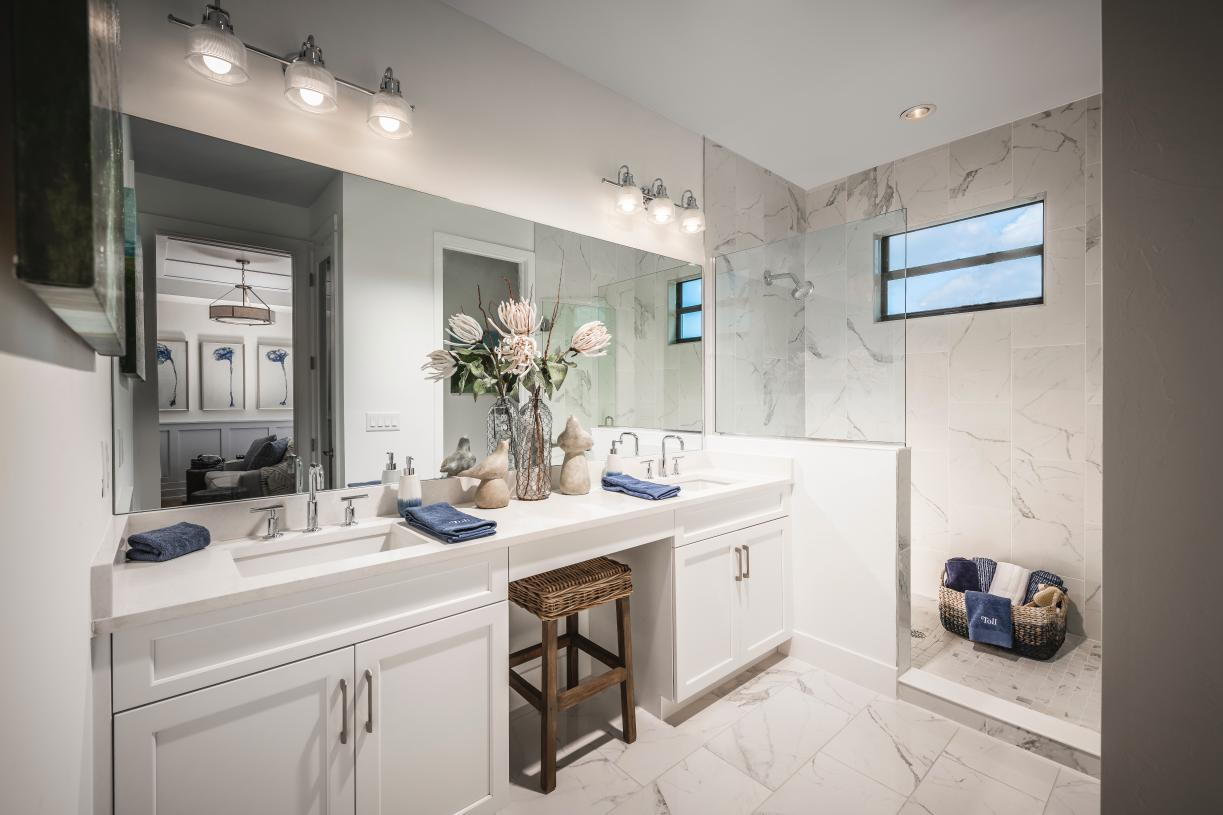 Primary bath with dual sinks, tile to ceiling, and private water closet