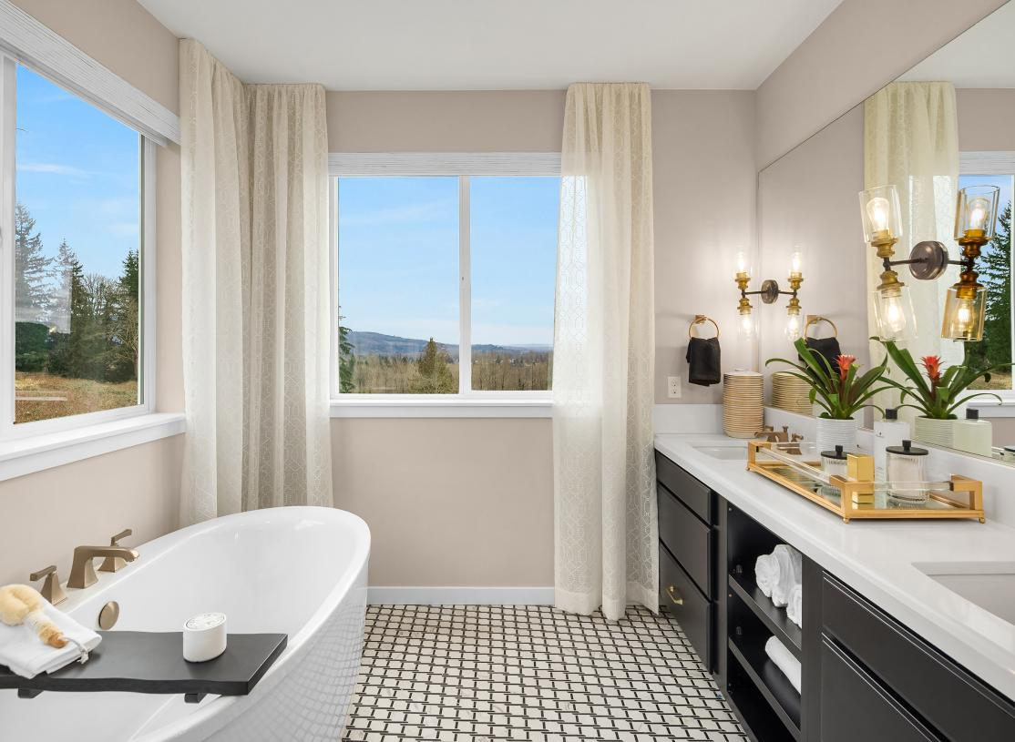 Bright windows fill the primary bathroom in natural light