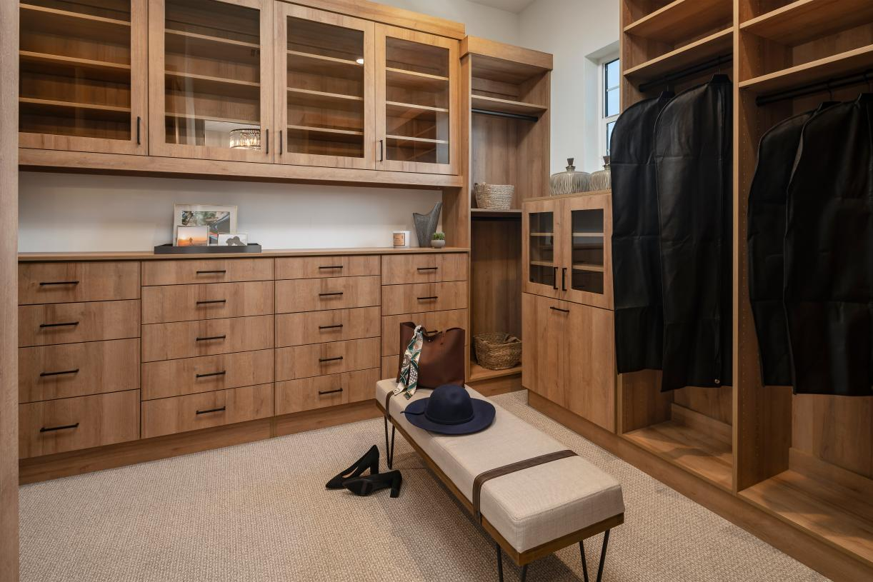 Spacious primary bedroom walk-in closet with built-in cabinets