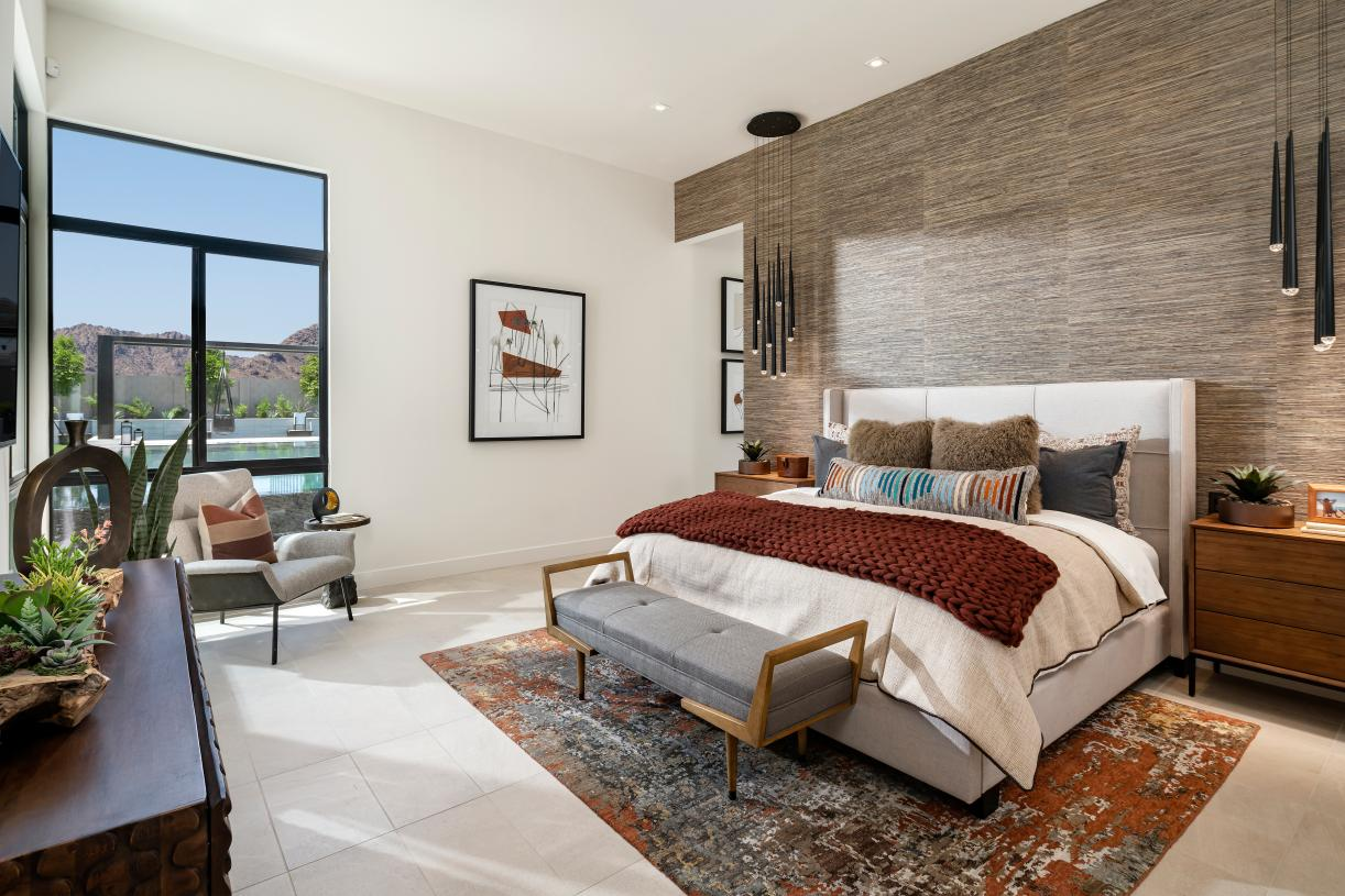 Luxurious primary bedroom suite with ample natural light and seating area