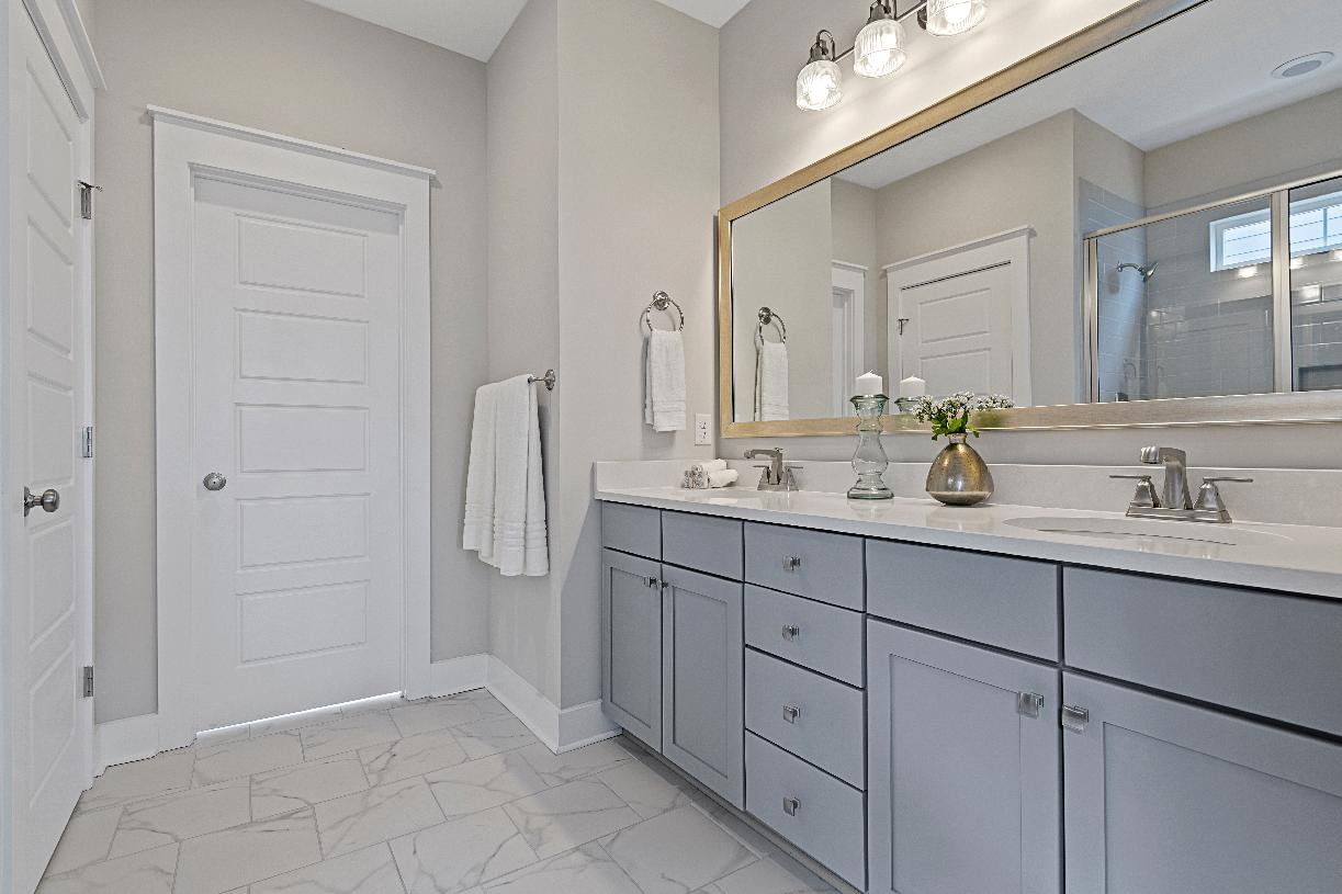 Luxurious primary bath with dual vanity and large walk-in closet