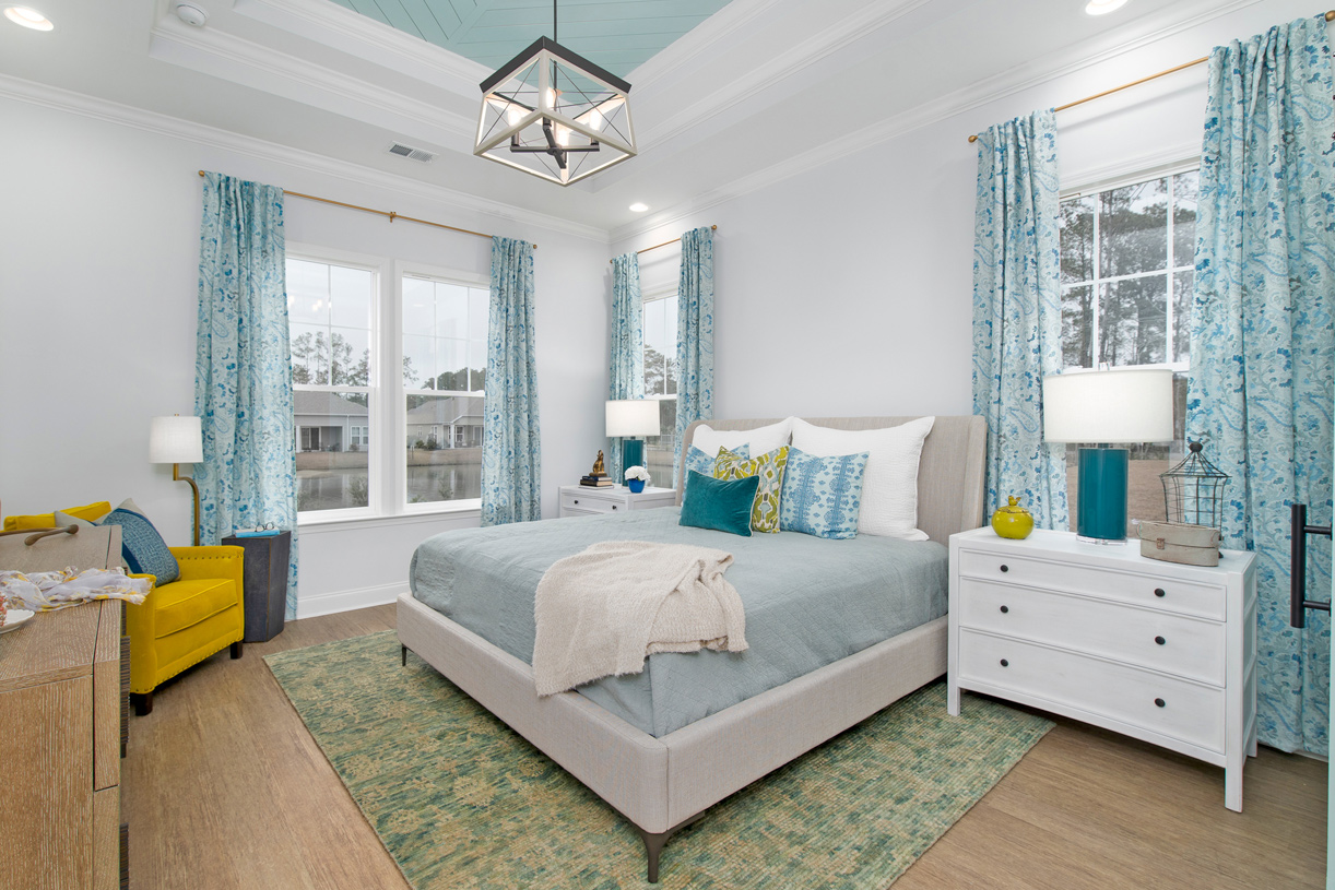 Spacious primary bedroom suites with ample natural light and a seating area