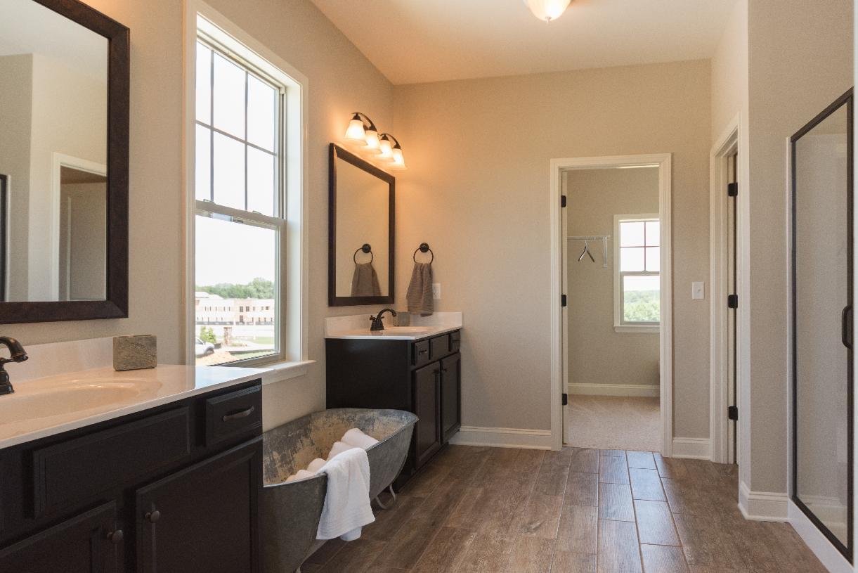 Lavish primary bathroom with dual-split vanity and large walk-in shower