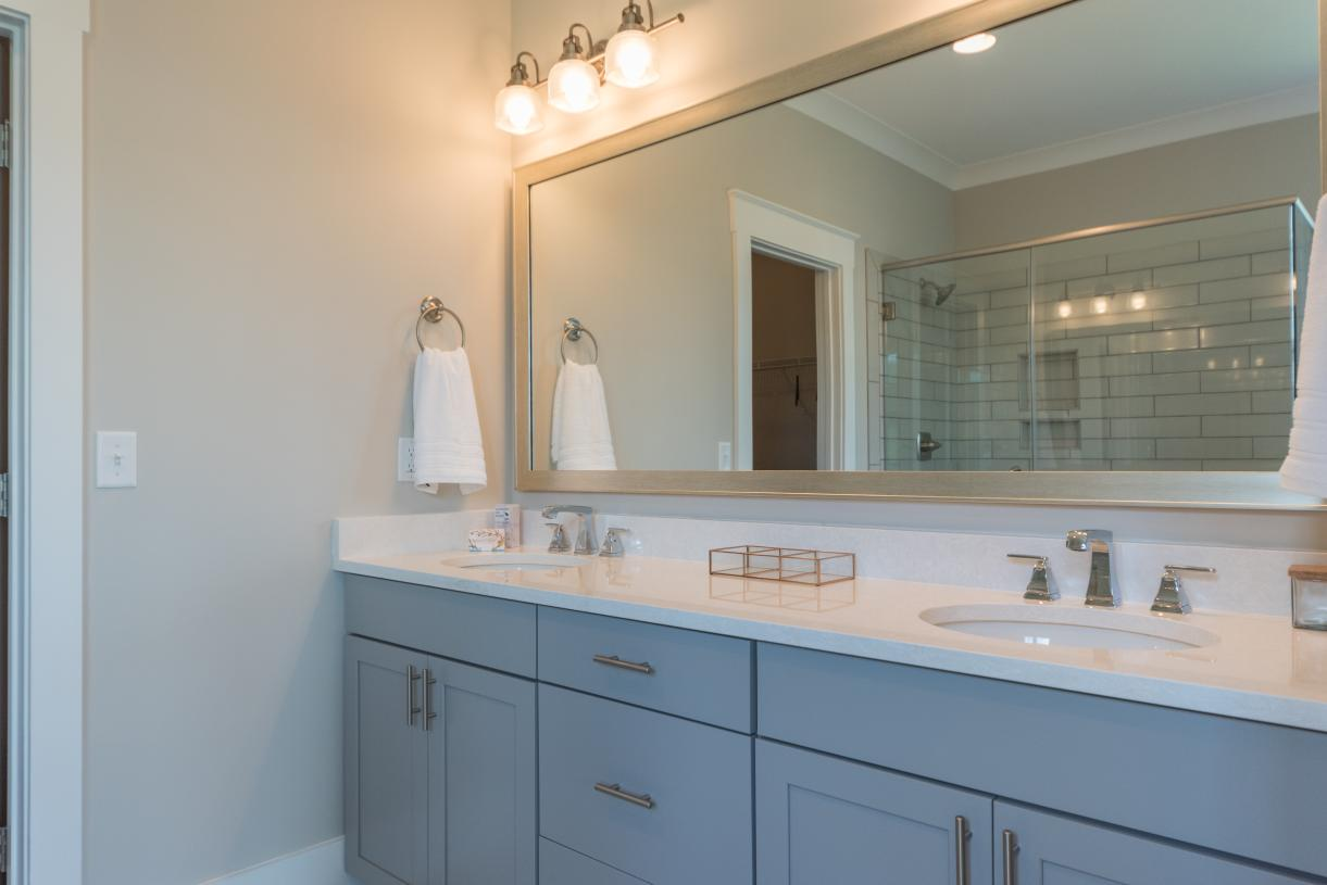 Lavish primary bathrooms with a large walk-in shower and ample countertop space