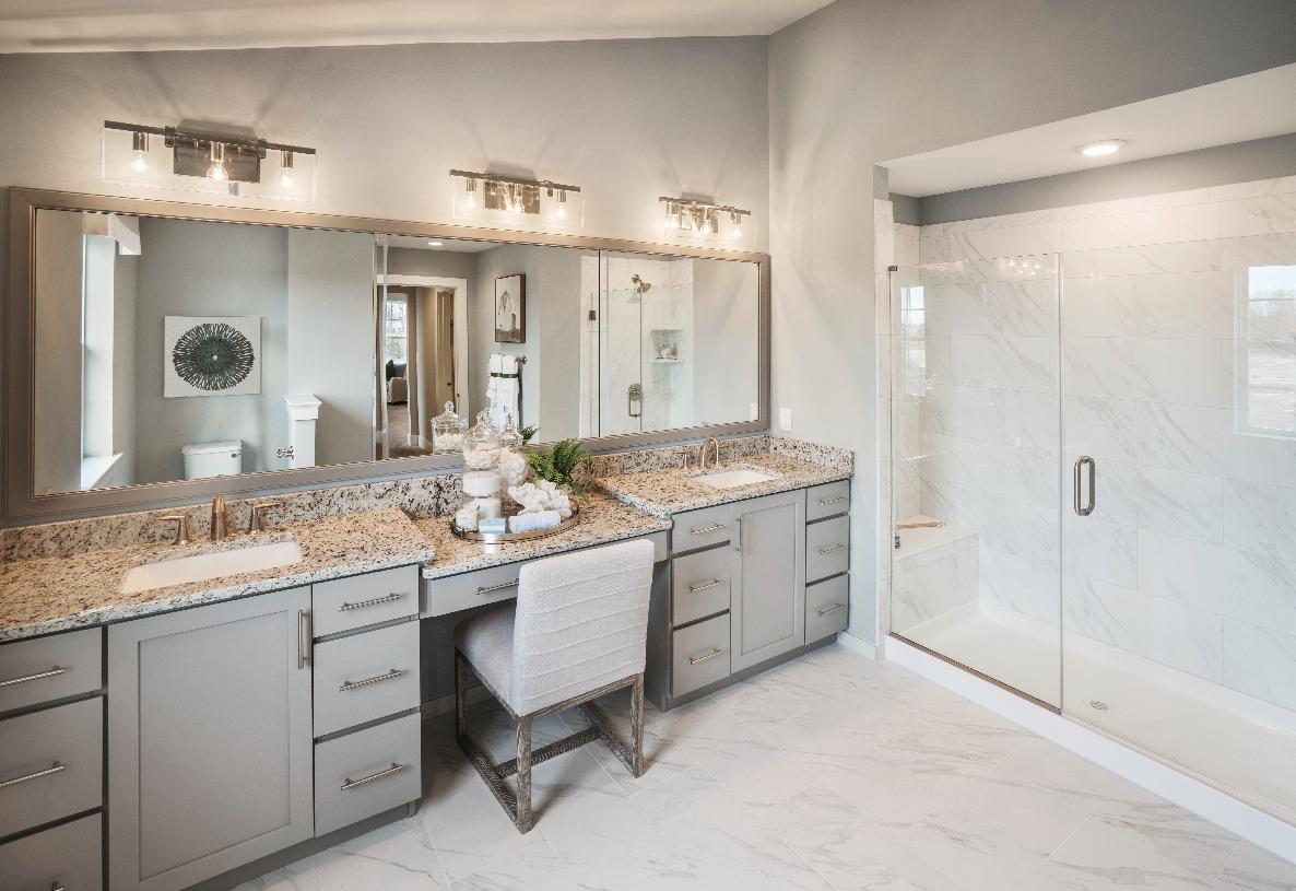 Spa-like primary bath with dual-sink vanity and luxe glass enclosed shower