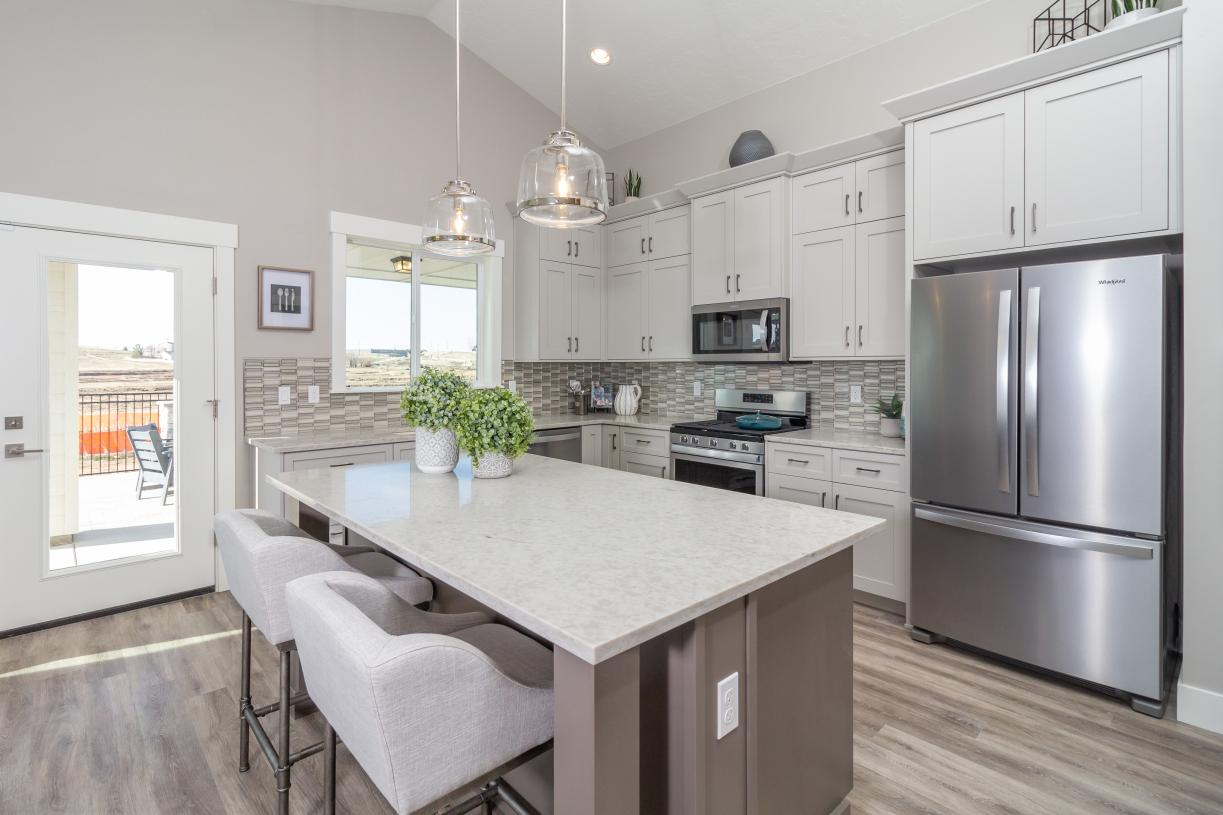 Open kitchen with designer lighting and custom cabinets