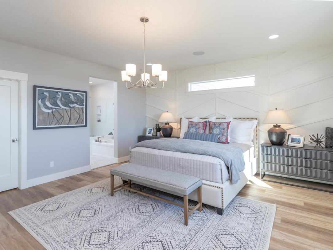 Spacious primary bedroom suite with designer lighting