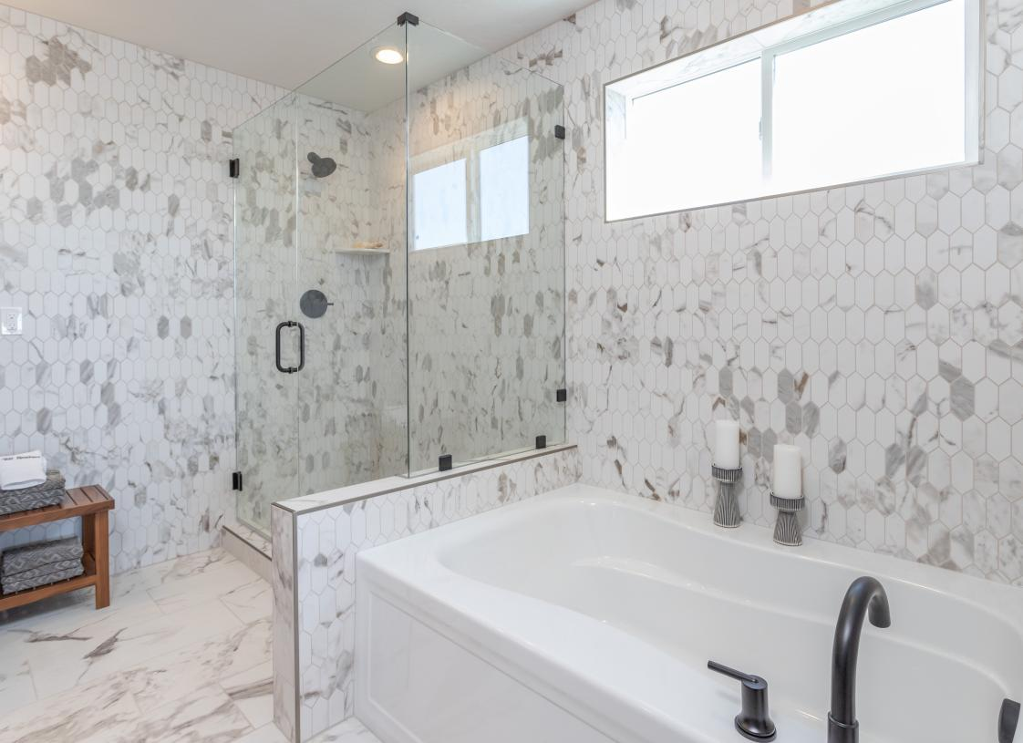 Separate bathtub and full-tiled shower in primary bathroom