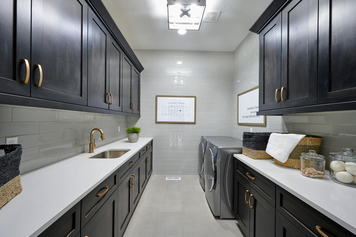 Luxury laundry room with sink and storage