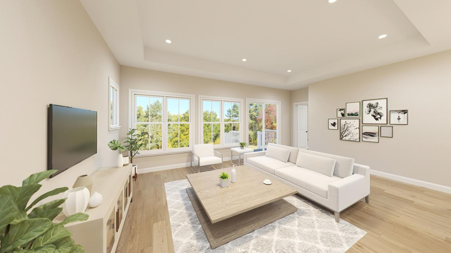 Sunlit great room enhanced with a tray ceiling