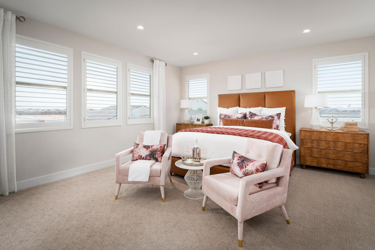 Beautiful primary bedroom suite with ample natural light and a seating area