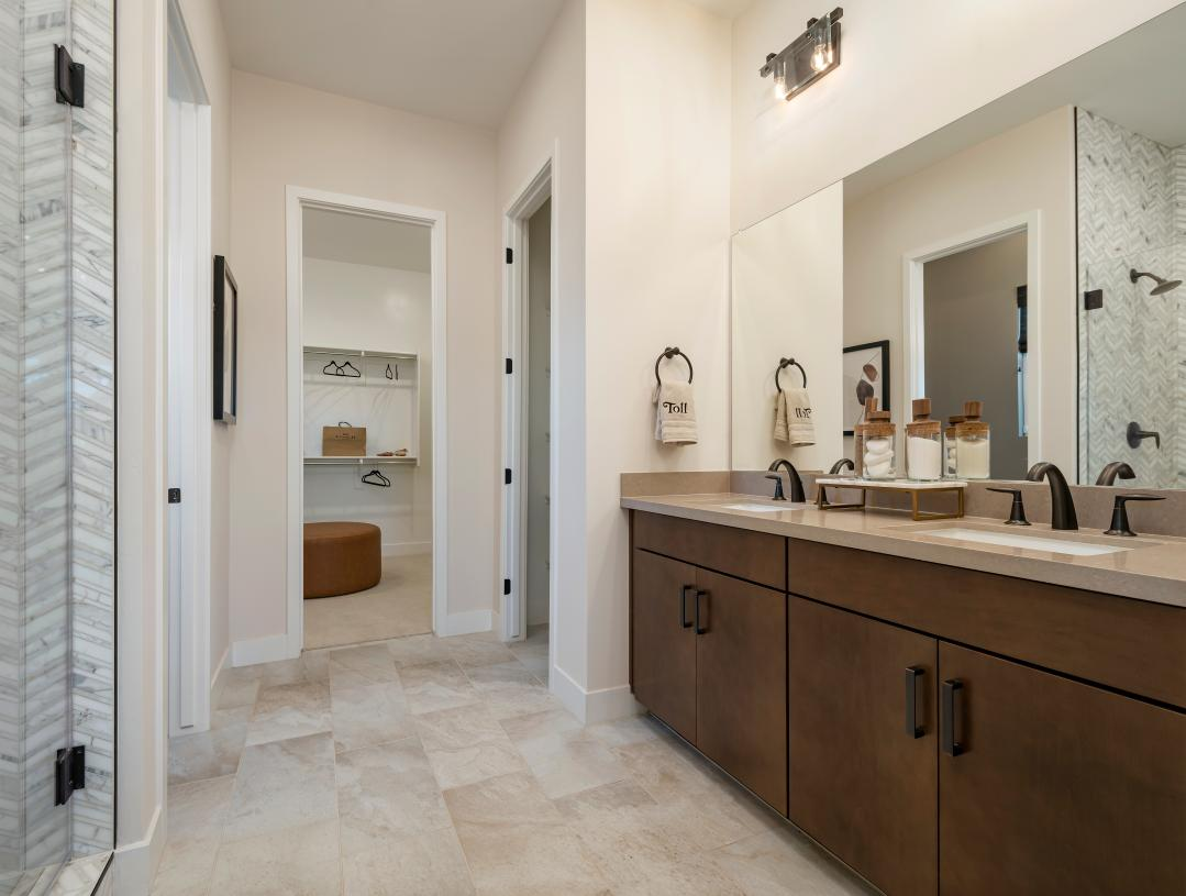 Lavish primary bathroom with large walk-in shower and closet