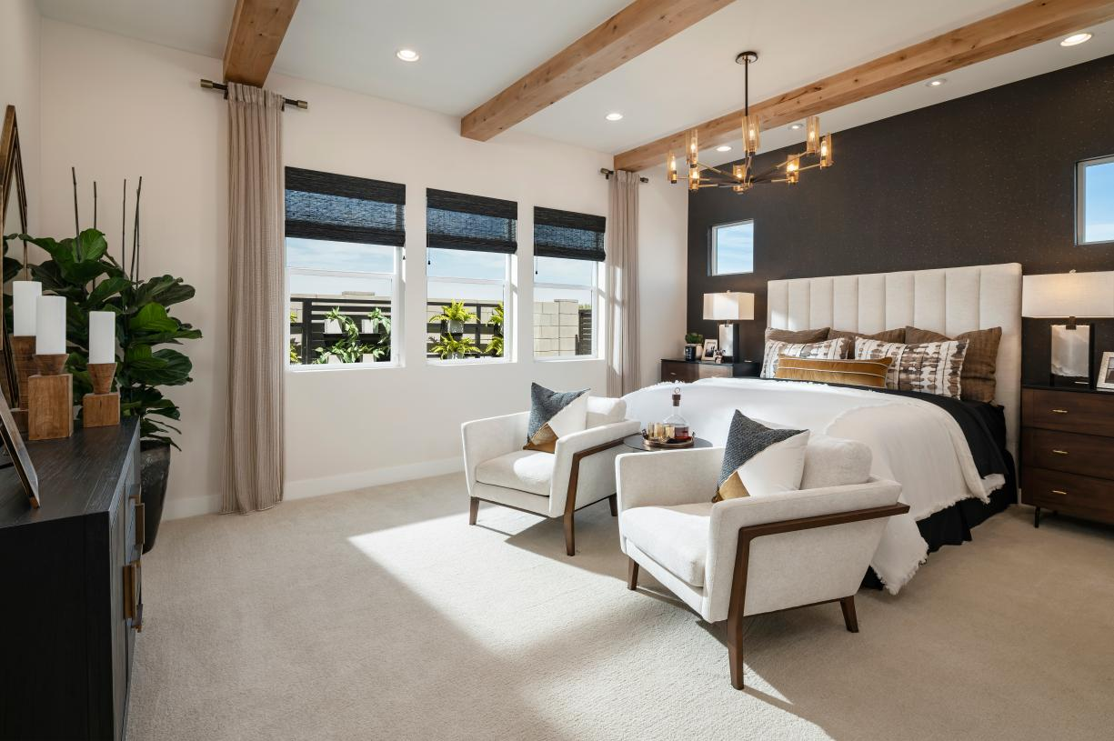 Stunning primary bedroom suite with ample natural light and a seating area