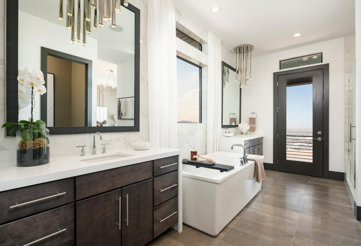 Luxurious primary bath with dual split sink vanity and access to the patio beyond