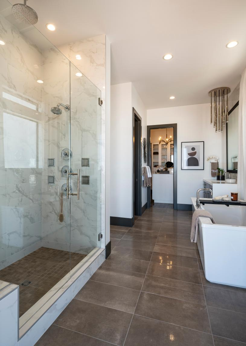 Lavish primary bathroom with glass-enclosed shower and freestanding tub