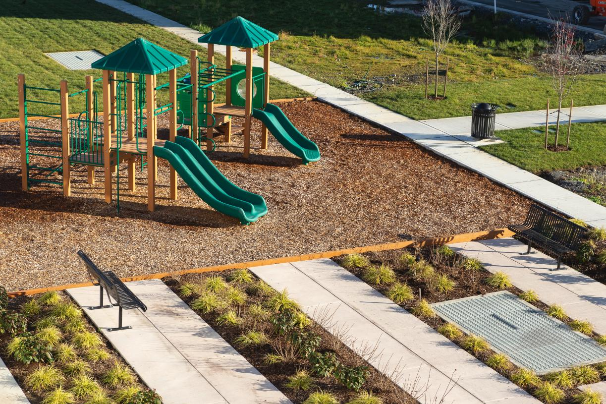 Walking paths connect residents to a central park with open lawn, playground structure, and picnic tables