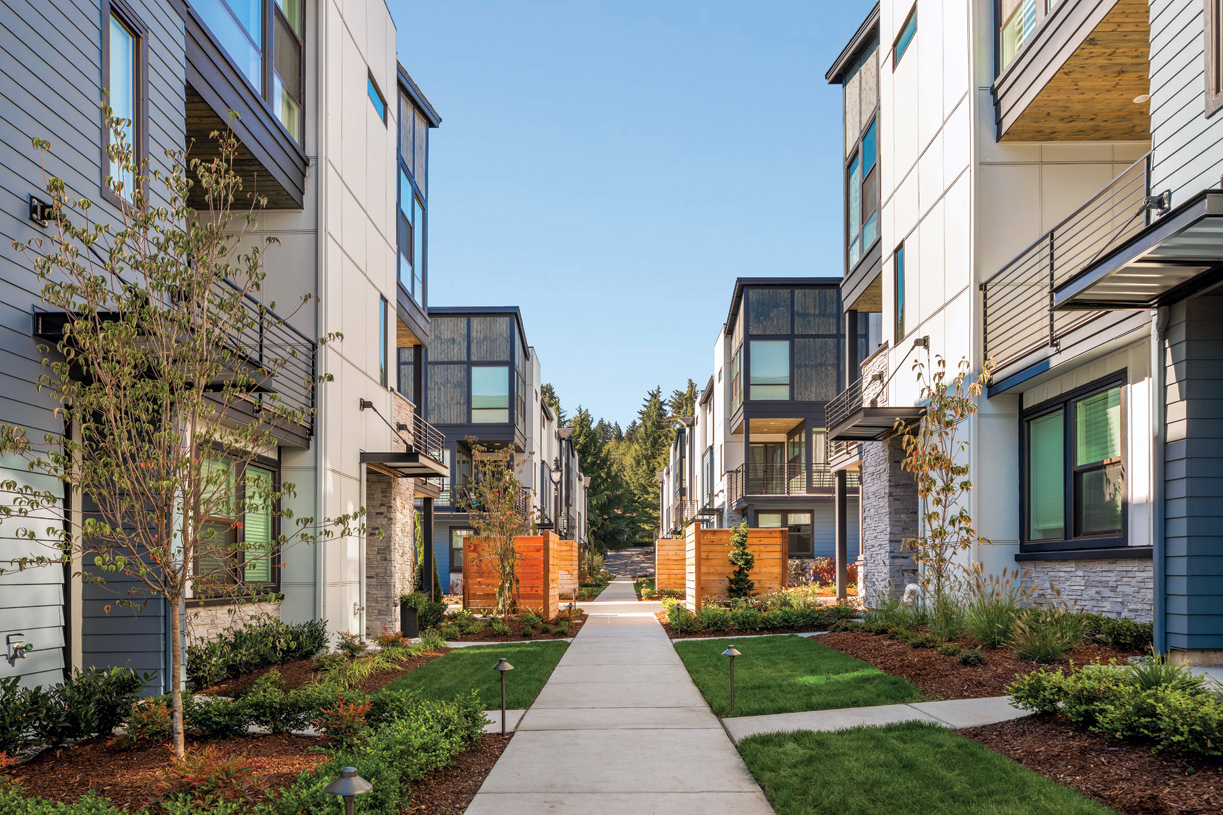 Walking paths connect the residents to a central park with open lawn, playground structure, and picnic tables