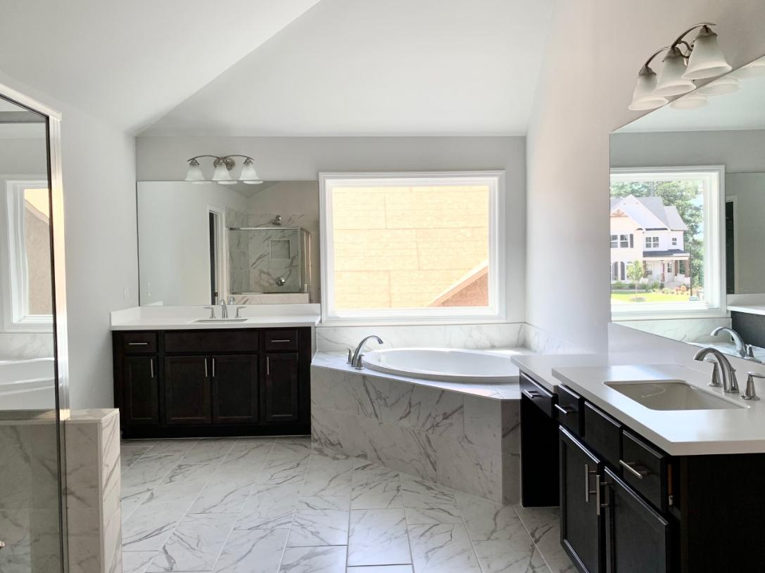 The primary bath features dual-sink vanity, free-standing tub, and large shower