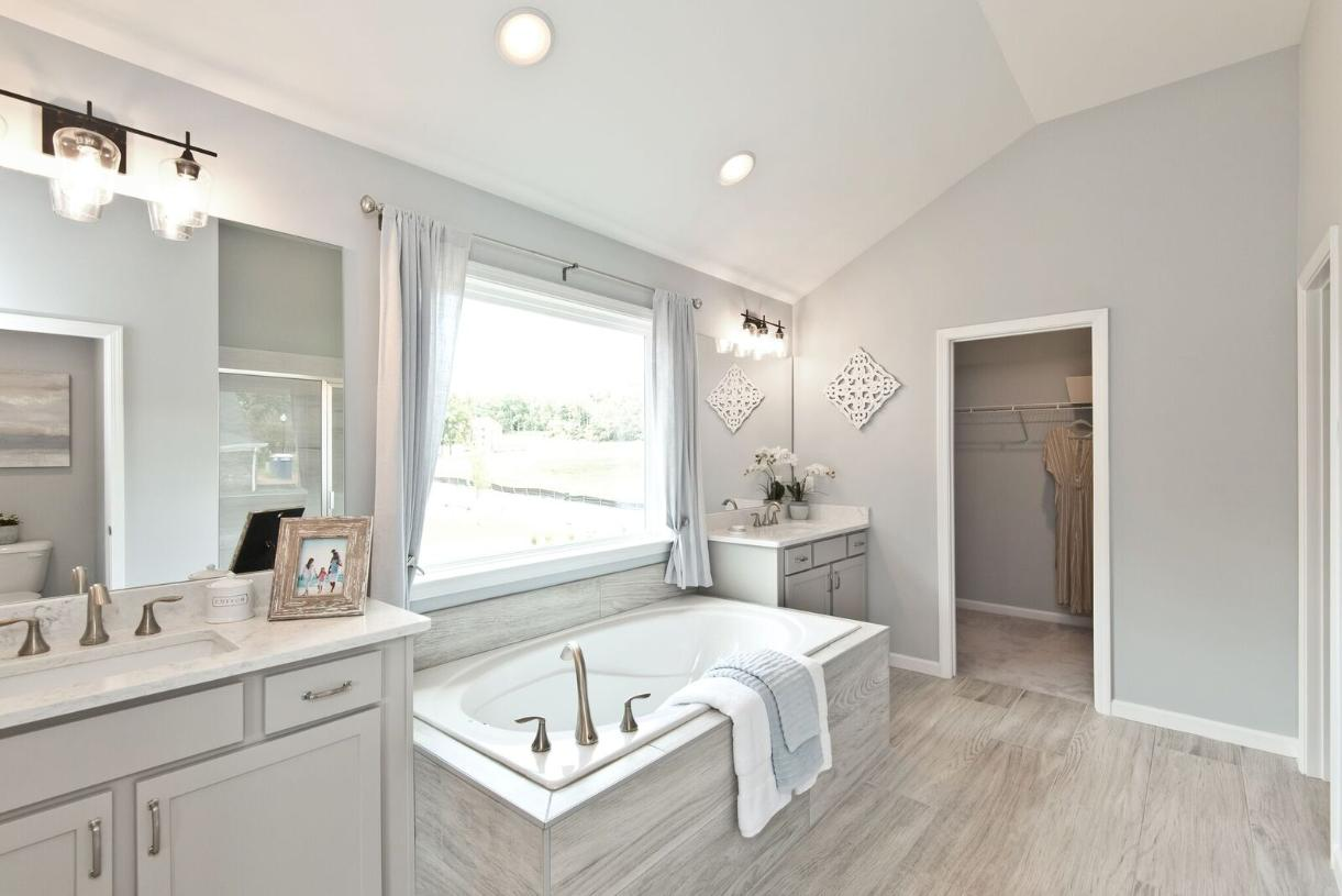 Luxurious primary bathroom with double vanities, soaking tub, and separate shower