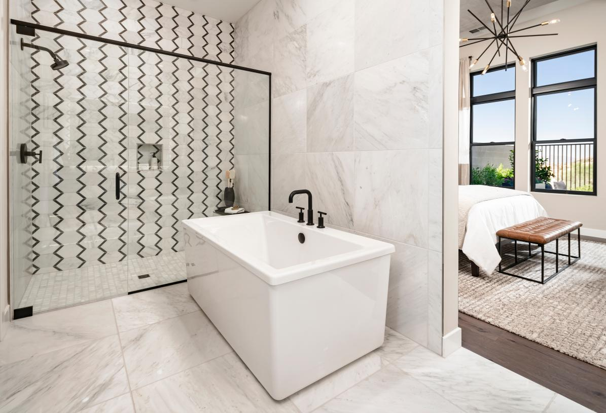 Spa-like primary bathroom features a large soaking tub and walk-in shower