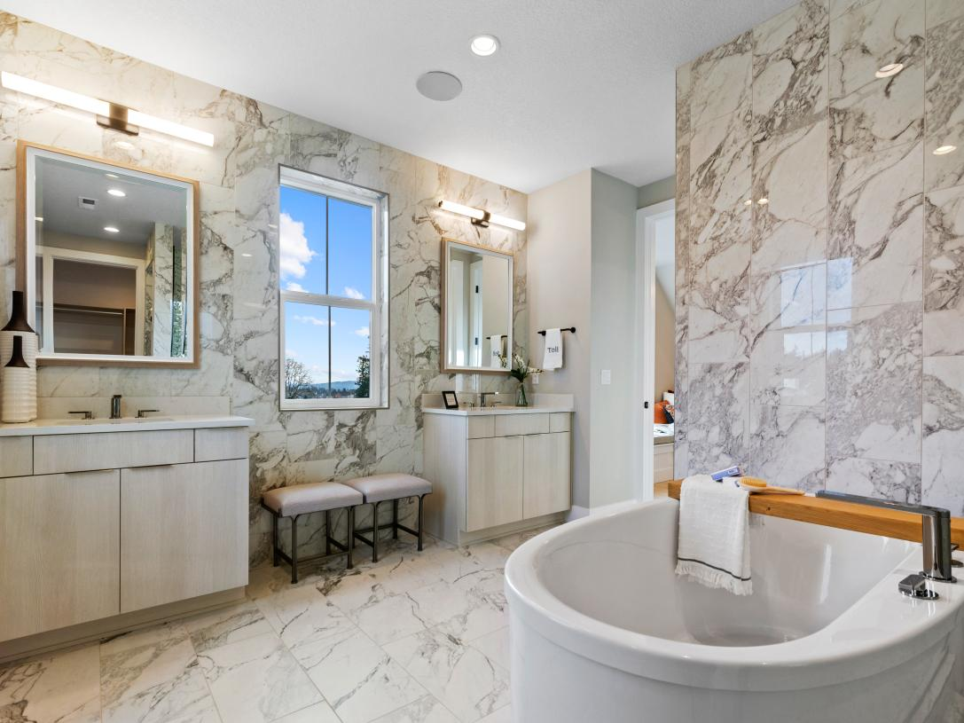 Luxe bathroom with dual vanities and free standing tub