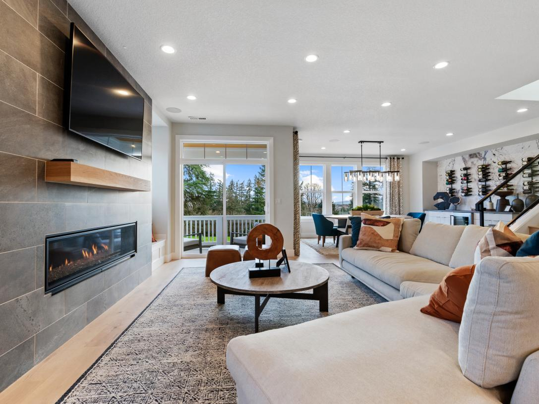 Living room with cozy fireplace and sliding glass door to covered deck