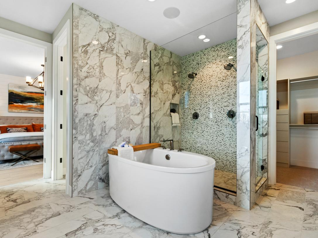 Spacious shower, freestanding oval tub and walk-in closet beyond