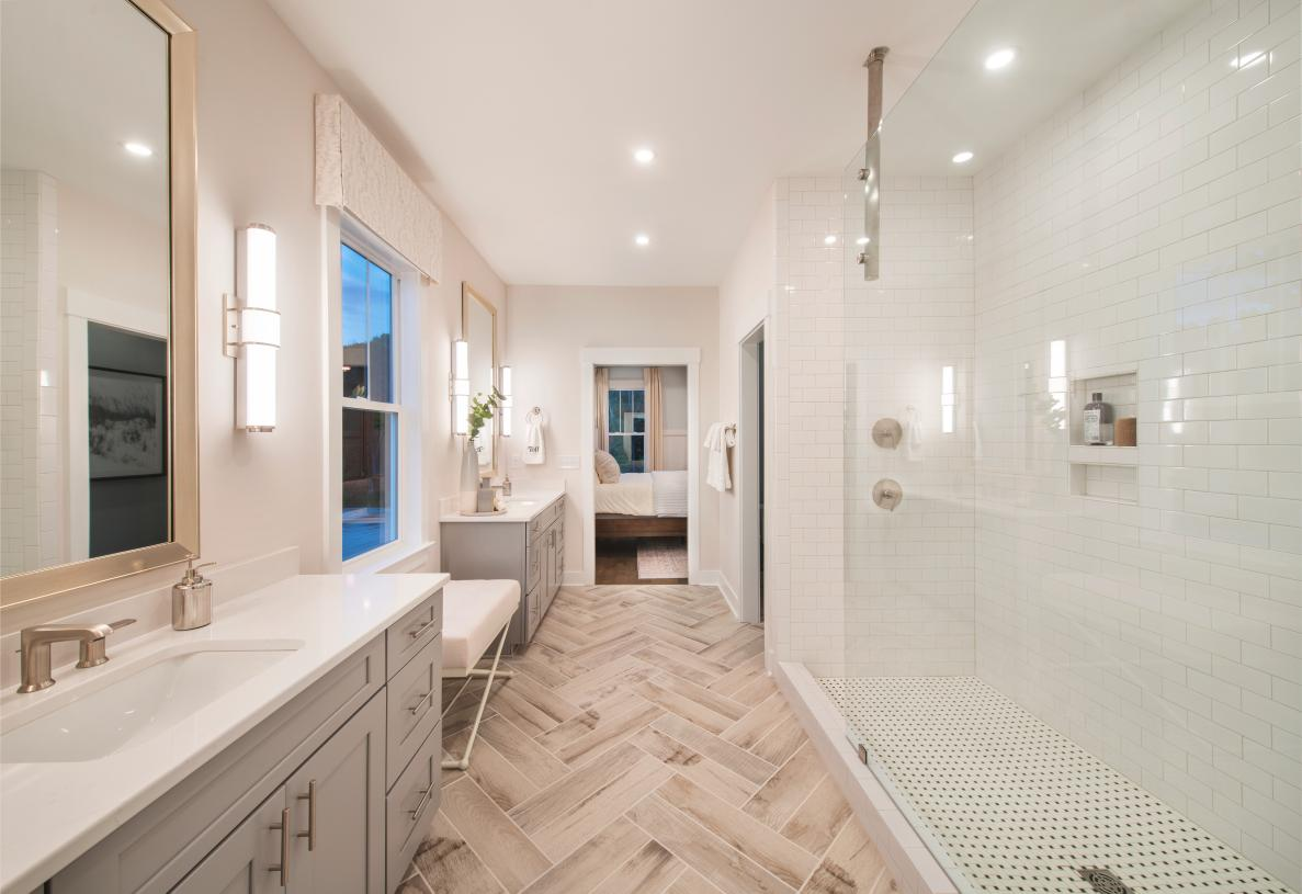 Lavish primary bathroom with split sinks, and huge walk-in shower