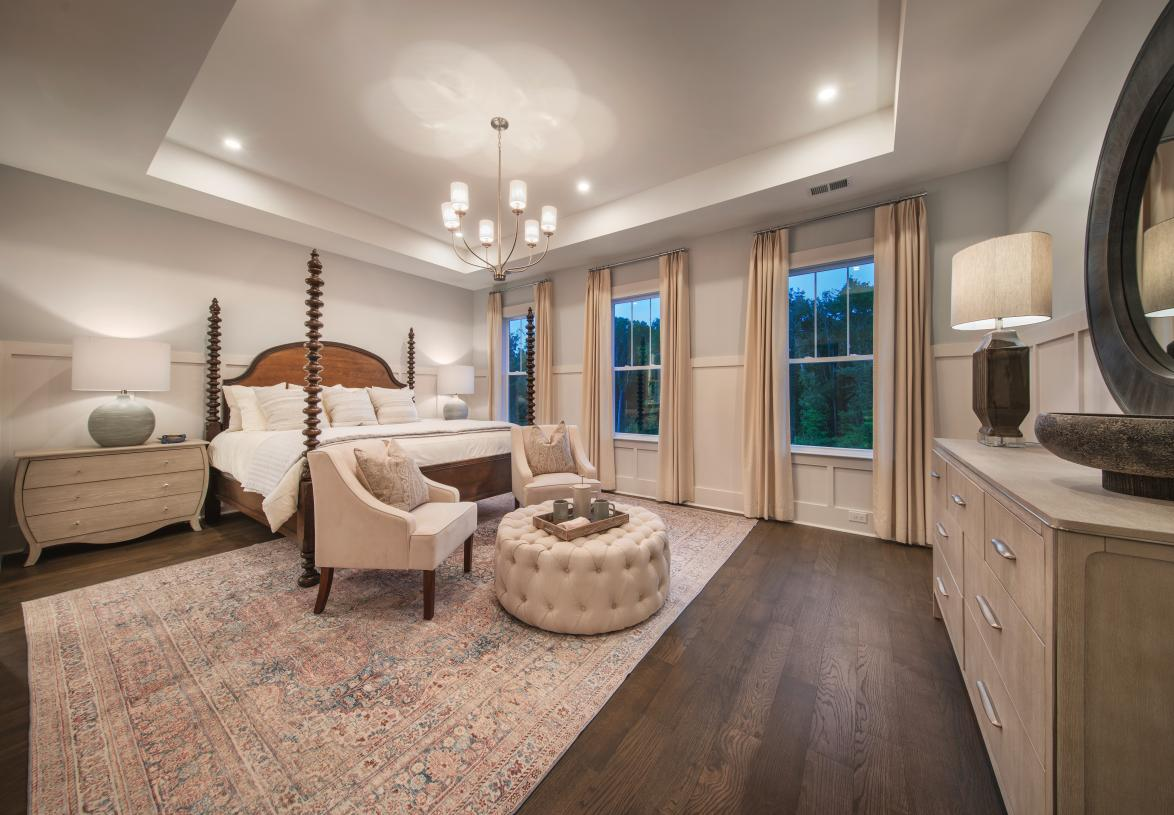 Gorgeous primary bedroom suite with a seating area, trey ceilings, and ample natural light