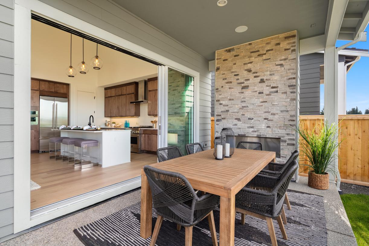 Covered patio with optional fireplace and 16' stacking doors provides year-round indoor-outdoor living