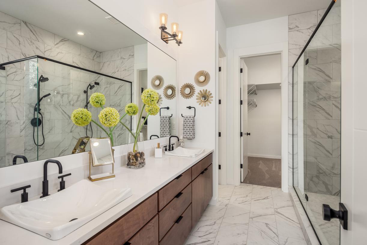 Luxe primary bathroom with adjacent walk-in closet
