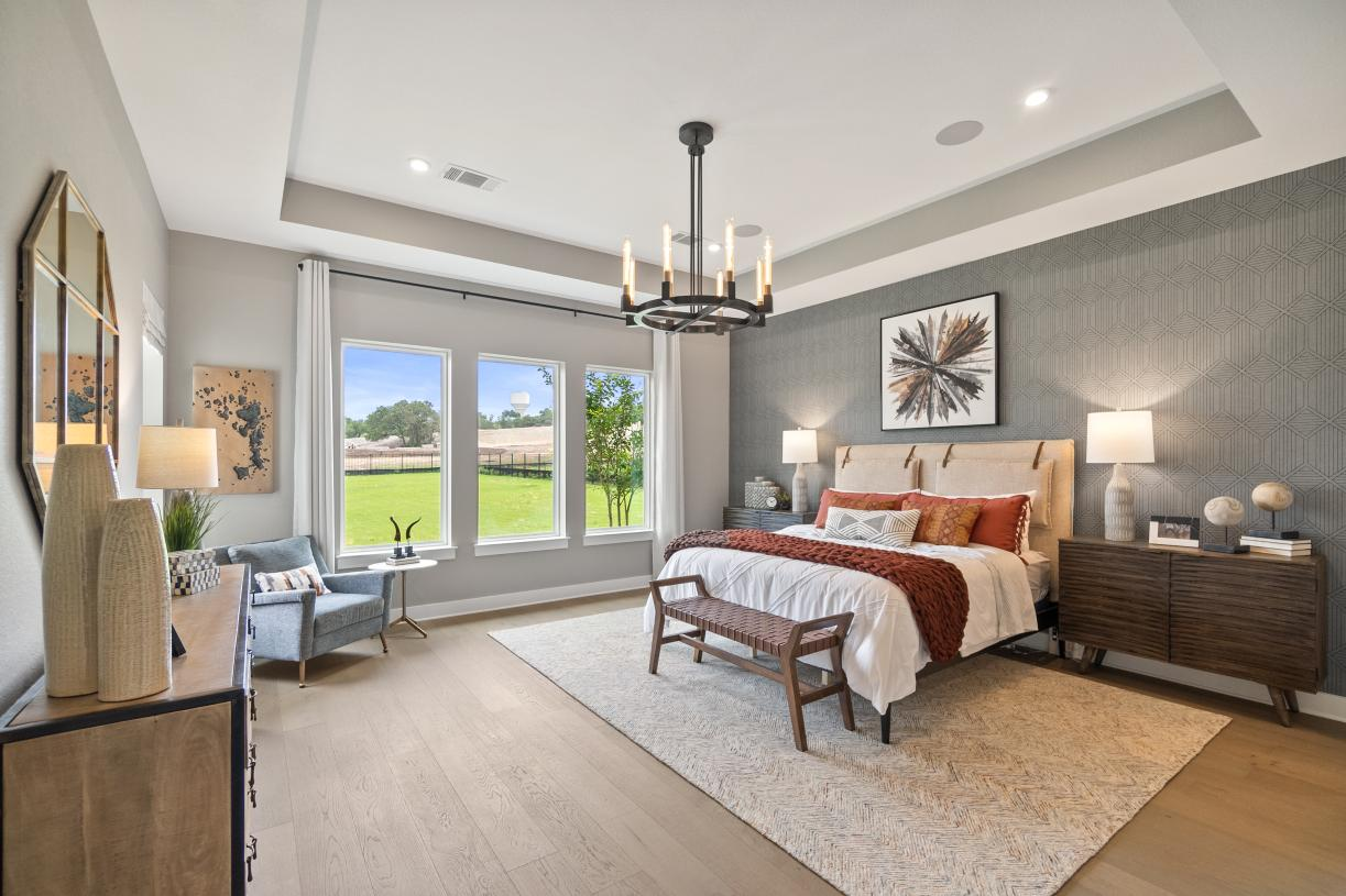 Primary bedroom suite is enhanced by a recessed ceiling