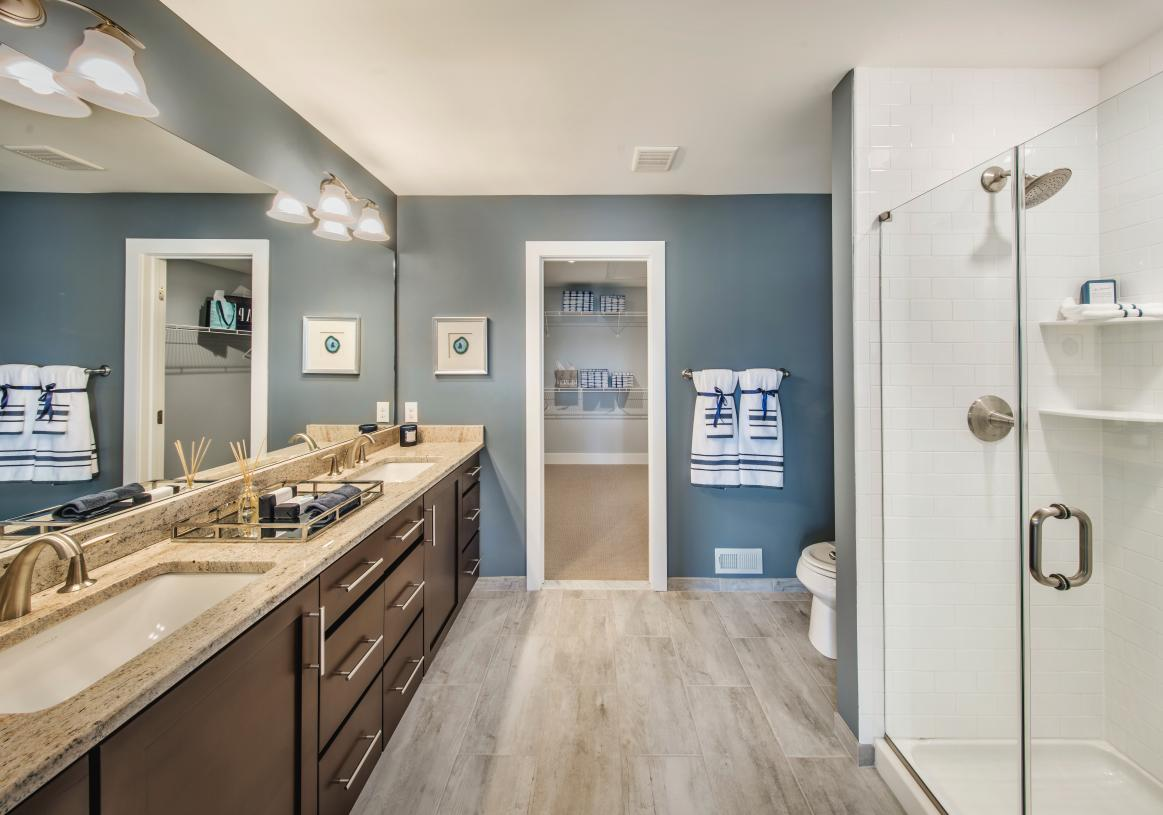 Spa-like primary bath with dual-sink vanity, large luxe shower, and linen storage