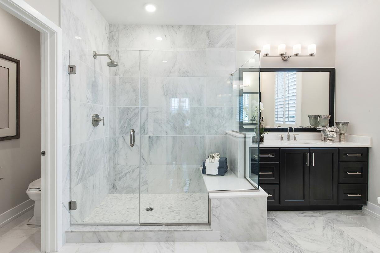 Primary bathrooms with dual sinks, glass enclosed showers and private water closets