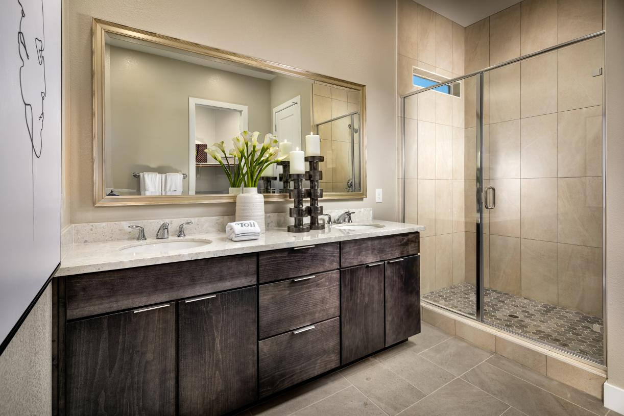 Primary baths with walk-in showers and dual vanities