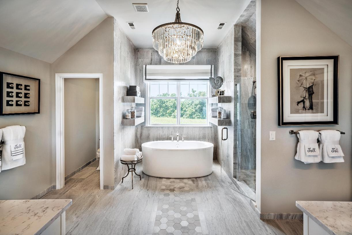 Lavish primary bath with soaking tub, large shower, and private toilet area