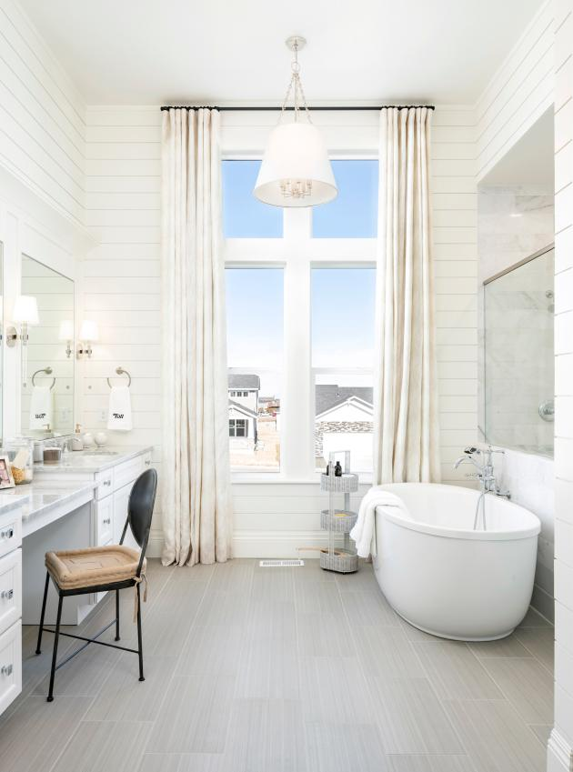 Lavish primary bathrooms with large walk-in showers and ample countertop space