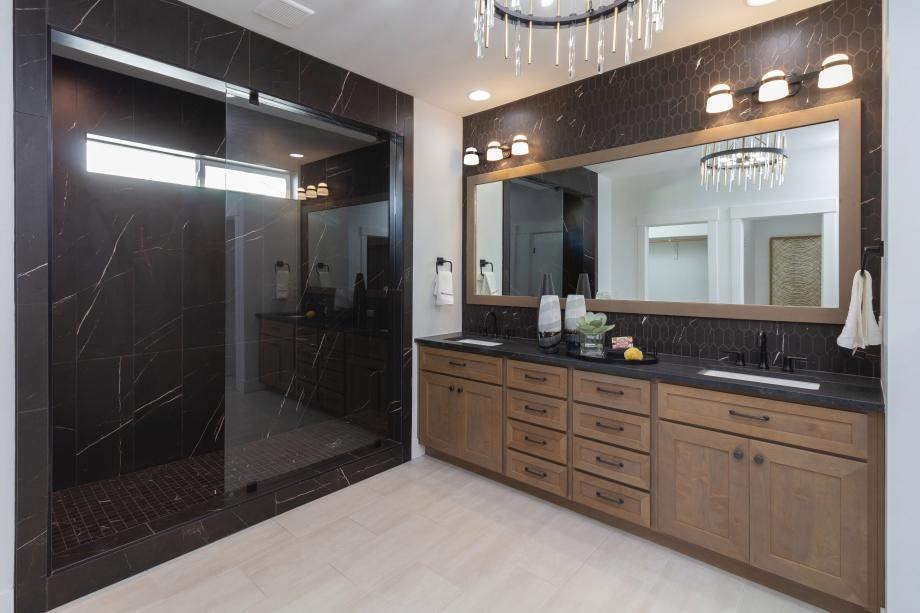 An expansive walk-in shower with high-contrast tile finishes adds opulence to this primary bath